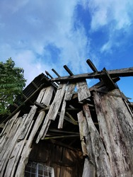 abandoned and dilapidated view of old wooden house with blue sky background