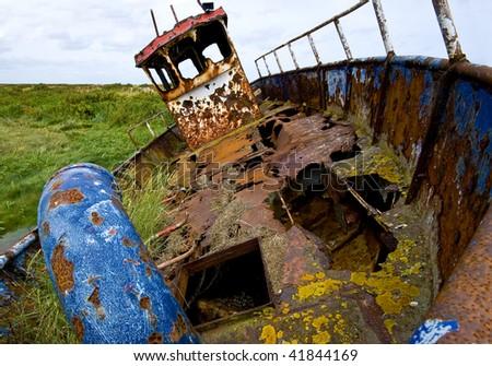 Abandoned and rusting fishing boat in Blakeney salt marsh, UK.