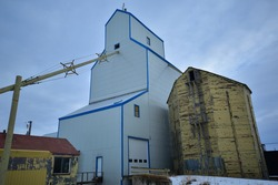 Abandoned antiquated grain elevators, old fashioned grain storage found in rural  community in Mosleigh, Alberta.