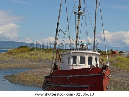 Abandoned boat grounded near the bay in summer with a bright blue sky