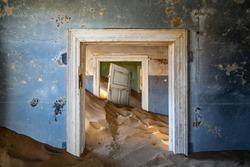 Abandoned building being taken over by encroaching sand in the Kolmanskop ghost town near Luderitz, Namib Desert, Namibia.