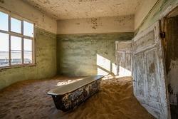 Abandoned building being taken over by encroaching sand in the old mining town of Kolmanskop near Luderitz, Namib Desert, Namibia.