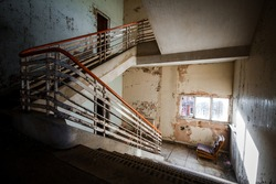 Abandoned building creepy dark moody staircase in dilapidated run down old deserted hospital school ruin with a single empty chair indoors on stairs landing no one there