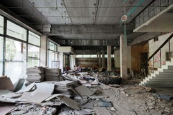 Abandoned building interior. Corridor perspective with dirt on the floor and broken windows