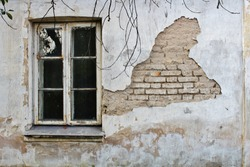 Abandoned building; wall of an old, damaged building; wall with a window in an old building