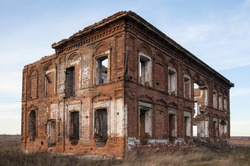 abandoned building with broken windows and without roof. Old red brick house in field. Old destroyed brick building with many empty windows on sky background