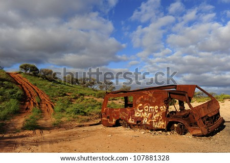 Abandoned burnt out car wreck in outback Australia, with beautiful sky as background and copy space.