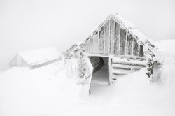 abandoned cabins in the fog after snow storm in Carpathian mountains