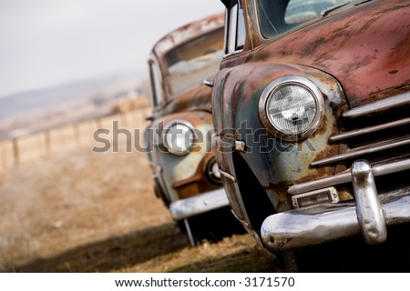abandoned cars, two vintage cars angled closeup with focus on headlight, rural Wyoming