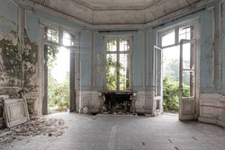 Abandoned castle, room with fireplace and large broken windows