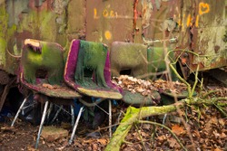 Abandoned chairs close-up. Very old chairs next to abandoned house in forest. Four overgrown padded chairs abandoned in the forest. Scary or horror place next to rusty steel mobile house in the woods.