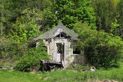 Abandoned child's playhouse photographed in the summer season.