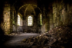 abandoned church interior where weeds and plants grow on the inside walls and windows. Crumbled bricks lay on the foreground