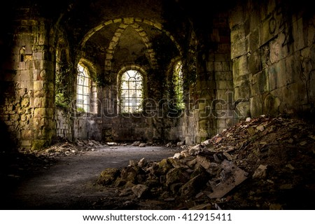 abandoned church interior where weeds and plants grow on the inside walls and windows. Crumbled bricks lay on the foreground #412915411