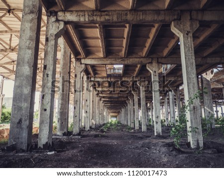 Abandoned concrete construction with columns like tunnel or corridor, toned