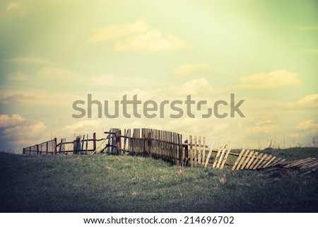 Abandoned countryside. Concept summer landscape with old broken fence at pasture under cloudy sky. Nature background in vintage style