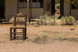 Abandoned, destroyed buildings at 6 road. Old, damaged chair in front of the house. Ghost town, Inyo National Forest. Nevada, USA