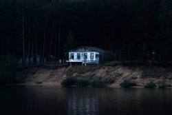 abandoned dilapidated house on a dark wooded bank is ready to collapse into the river