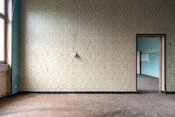 Abandoned empty room with flowery wallpaper