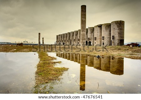 Abandoned facility under moody cloudy dark sky, image of decrepitude