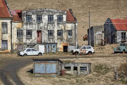 Abandoned farm house ruins in Iceland with rusty vehicles around