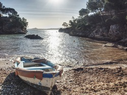 Abandoned fishing boat in rocky bay against sun. Rocky walls with private villa above round bay. Boat on a sandy beach by the sea, Mallorca island