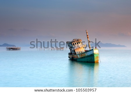 Abandoned fishing boat in the sea, thailand - stock photo
