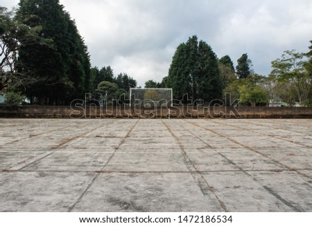 Abandoned football field with nobody, desert, wild, not maintained place, perspective point of view, line of concrete, center picture.
