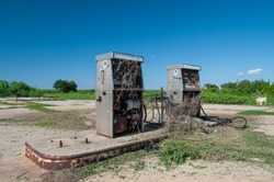 Abandoned Gas Station Pumps in Empty parking lot surrounded by blue sky and bushes