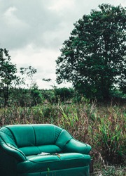 Abandoned green sofa left in the forest for a long time. This is ancient and vintage.