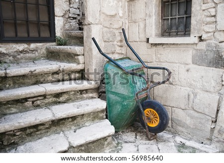 Abandoned green wheelbarrow.