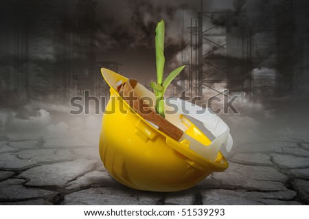 Abandoned helmet with a sprout coming out in a dead soil of a very polluted environment