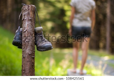 Abandoned hiking shoes with a woman walking bare feet