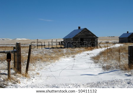Abandoned homestead on open prairie land has open doors and windows.  Barbed wire fence covers old driveway.  Snow lays on drive and in field.  Open mail box hangs unused.