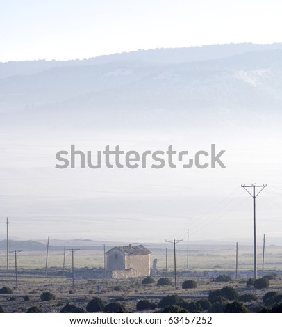 abandoned house and telephone poles through the fog with hills