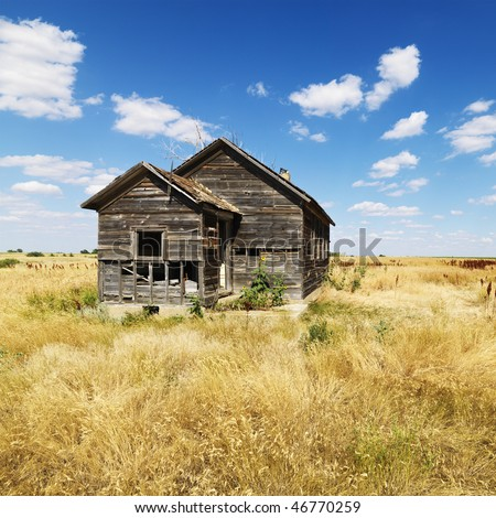 Abandoned house in state of disrepair in field in rural North Dakota. Square format.