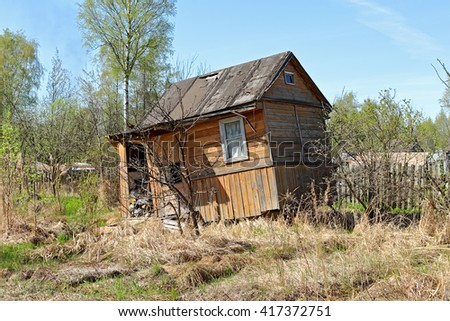 Abandoned house. Old garden plot. A broken fence. poor housing. poverty. rustic. stock photo