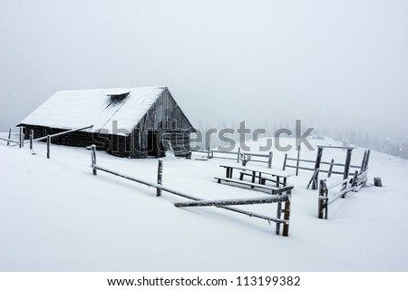 Abandoned house on the slope covered with snow