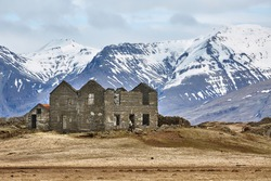 Abandoned house ruins in Iceland with mountains in the background