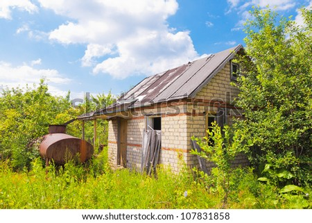 Abandoned hut among trees and bushes in summertime