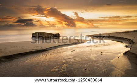 Abandoned Japanese concrete bunker half sunk in the beach with sunrise as a background.