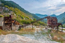Abandoned lime kiln from the time of socialism in Bulgaria - abandoned, broken and rusty industrial limestone grinding machine for lime