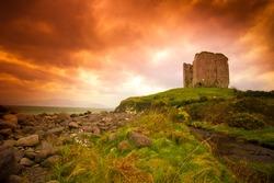 Abandoned medieval castle on Ireland Dingle coast under idyllic sunset