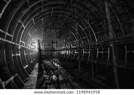 Abandoned metro tunnel with metal racks, in backlight. Urban Abstract Geometry. Monochrome.