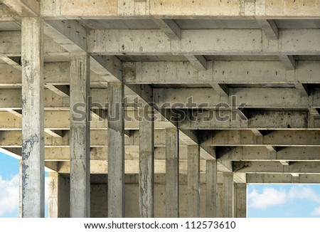 Abandoned modern construction - empty house at blue sky background. Reinforced concrete structure of the upper floors of building under construction - supporting columns and galleries empty space.
