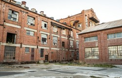 Abandoned multi-story red brick factory building with broken glass windows.