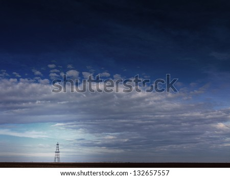 Abandoned oil rig profiled on cloudy day sky