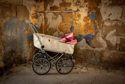 Abandoned old antique baby carriage against the background of old walls in an abandoned house