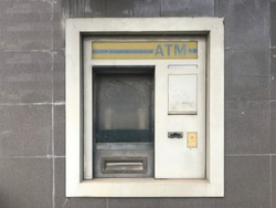 Abandoned old ATM machine in urban city. Dirty automatic teller machine.