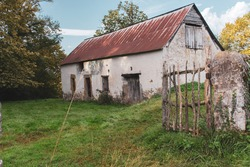 Abandoned old barn with wooden fence and grass on backyard. Weathered exterior of ancient building in village. Rural landmark. Rustic architecture in France. Travel in provence, France. Countryside.